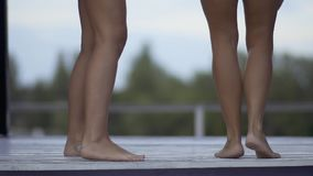 两个跳舞的苗条被晒黑的对女性腿 女孩获得在休息室的乐趣在游泳场附近一个周末 影视素材