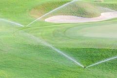 两个运作在绿色高尔夫球场的喷水隆头供水系统 库存照片
