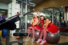 两个运动的女孩在健身房的圣诞老人服装在圣诞节 图库摄影
