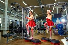 两个运动的女孩在健身房的圣诞老人服装在圣诞节 免版税库存图片