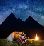 两个远足者有休息在他的阵营在晚上在营火附近下发光满天星斗的天空 免版税库存图片