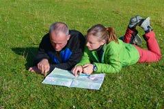 两个远足者读旅行的地图 库存照片