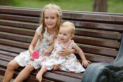 两个迷人的姐妹白肤金发的女孩坐在summe的一条长凳 库存照片