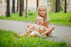 两个迷人的拥抱和笑在gra的姐妹白肤金发的女孩 免版税库存照片