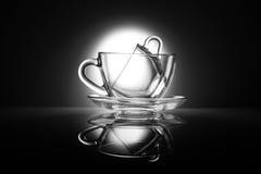 两个透明茶杯由玻璃制成在与反射的一张桌 黑白厨房项目 免版税库存照片