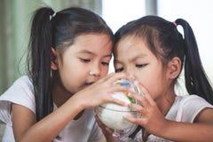 两个逗人喜爱的亚裔儿童女孩在教室使用放大器看和学习地球 库存图片