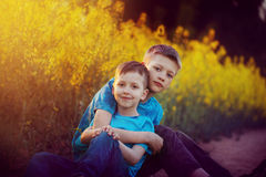两个逗人喜爱的兄弟姐妹男孩拥抱和获得乐趣在油菜领域附近 一起可爱的朋友在晴朗的温暖的夏日 兄弟lo 免版税库存图片