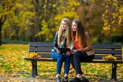 两个逗人喜爱的女学生女孩坐一条长凳在秋天公园 免版税库存照片