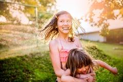 两个逗人喜爱的女孩获得乐趣外面在夏天庭院 图库摄影