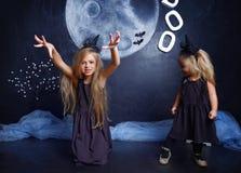 两个逗人喜爱的妹在巫婆服装打扮 库存照片