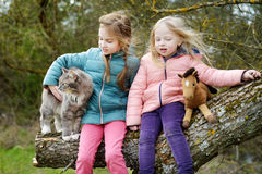 两个逗人喜爱的妹坐与他们的宠物猫的一本树日志 免版税库存照片