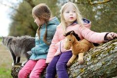 两个逗人喜爱的妹坐与他们的宠物猫的一本树日志 库存图片