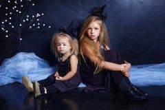 两个逗人喜爱的妹女孩在巫婆衣服在演播室坐黑背景 日历概念日期冷面万圣节愉快的藏品微型收割机说大镰刀身分 免版税库存图片