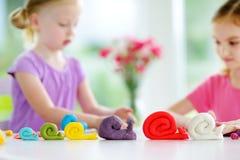 两个逗人喜爱的妹获得乐趣与五颜六色的雕塑黏土一起在托儿 在家铸造创造性的孩子 库存图片