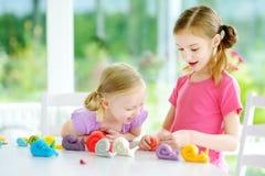 两个逗人喜爱的妹获得乐趣与五颜六色的雕塑黏土一起在托儿 库存照片