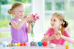 两个逗人喜爱的妹获得乐趣与雕塑黏土一起在托儿 在家铸造创造性的孩子 与pla的儿童游戏 免版税库存照片