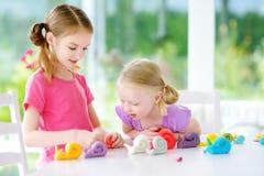 两个逗人喜爱的妹获得乐趣与雕塑黏土一起在托儿 在家铸造创造性的孩子 与pla的儿童游戏 免版税库存图片