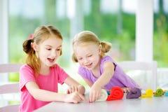 两个逗人喜爱的妹获得乐趣与雕塑黏土一起在托儿 在家铸造创造性的孩子 与pla的儿童游戏 库存图片