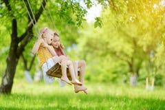 两个逗人喜爱的妹获得在摇摆的乐趣一起在美丽的夏天庭院在温暖和晴天户外 库存照片