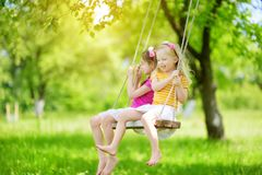 两个逗人喜爱的妹获得在摇摆的乐趣一起在美丽的夏天庭院在温暖和晴天户外 图库摄影