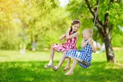 两个逗人喜爱的妹获得在摇摆的乐趣一起在美丽的夏天庭院在温暖和晴天户外 库存图片