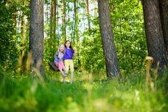 两个逗人喜爱的妹获得在摇摆的乐趣一起在美丽的夏天庭院在温暖和晴天 免版税图库摄影