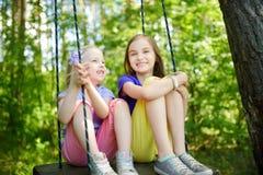 两个逗人喜爱的妹获得在摇摆的乐趣一起在美丽的夏天庭院在温暖和晴天 库存照片