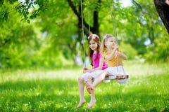 两个逗人喜爱的妹获得在摇摆的乐趣一起在美丽的夏天庭院 免版税图库摄影