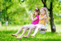 两个逗人喜爱的妹获得在摇摆的乐趣一起在美丽的夏天庭院 免版税库存照片