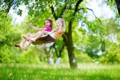 两个逗人喜爱的妹获得在摇摆的乐趣一起在美丽的夏天庭院 图库摄影