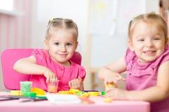 两个逗人喜爱的学龄前儿童姐妹获得乐趣与五颜六色的雕塑黏土一起在托儿 铸造创造性的孩子  库存照片
