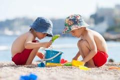 两个逗人喜爱的孩子,使用在海滩的沙子 免版税库存照片
