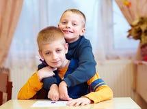 两个逗人喜爱的孩子,朋友在为孩子的修复学校与特别需要 图库摄影