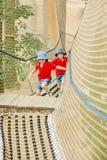 两个逗人喜爱的孩子,男孩兄弟,上升在绳索操场s 免版税库存照片