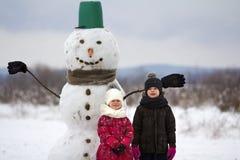 两个逗人喜爱的孩子,男孩和女孩,站立在桶帽子、围巾和手套的微笑的雪人前面在多雪的冬天的风景 免版税库存图片
