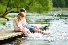 两个逗人喜爱的小女孩坐一个木平台由河或湖在水中的浸洗他们的脚在温暖的夏日 免版税库存图片