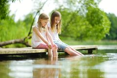 两个逗人喜爱的小女孩坐一个木平台由河或湖在水中的浸洗他们的脚在温暖的夏日 免版税库存照片