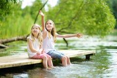 两个逗人喜爱的小女孩坐一个木平台由河或湖在水中的浸洗他们的脚在温暖的夏日 库存照片