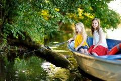 两个逗人喜爱的小女孩获得乐趣在小船由河美好的夏天晚上 库存图片
