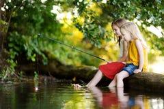 两个逗人喜爱的小女孩获得乐趣由河美好的夏天晚上 库存照片