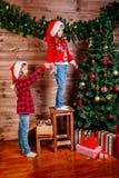 两个逗人喜爱的小孩女孩装饰圣诞树户内 免版税库存图片