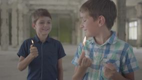 两个逗人喜爱的男孩在一间发烟性被放弃的屋子 有一次灼烧的比赛的,第二一个男孩与一个灼烧的打火机 影视素材