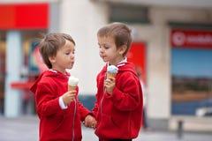 两个逗人喜爱的男孩,吃在街道上的冰淇凌 免版税图库摄影