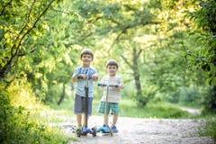 两个逗人喜爱的男孩,在骑马滑行车竞争,室外在公园,夏令时 免版税库存照片