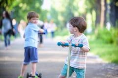两个逗人喜爱的男孩,在骑马滑行车竞争,室外在公园,夏令时 库存图片