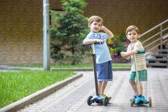 两个逗人喜爱的男孩,在骑马滑行车竞争,室外在公园,夏令时 免版税图库摄影