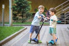 两个逗人喜爱的男孩,在骑马滑行车竞争,室外在公园, 库存照片