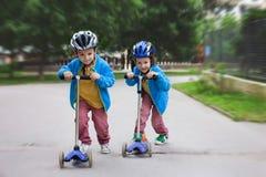 两个逗人喜爱的男孩,在骑马滑行车竞争,室外在公园 免版税图库摄影