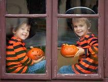 两个逗人喜爱的男孩,坐与起重器o灯笼的一个窗口 库存照片