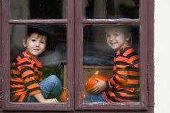 两个逗人喜爱的男孩,坐与起重器o灯笼的一个窗口 库存图片